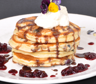 Blueberry Pancakes with cream, chocolate sauce and berry compote